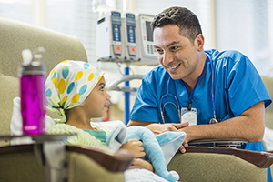 Healthcare provider talking with girl receiving chemotherapy.