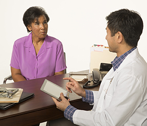 Healthcare provider with electronic tablet talking to woman.