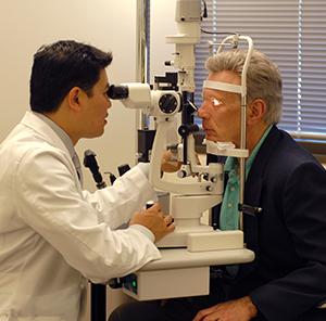Heathcare provider examining man's eyes.