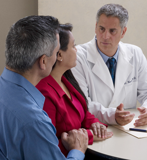 A man and woman discussing treatment plan with a healthcare provider.