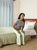 Woman sitting at edge of bed preparing to stand up.
