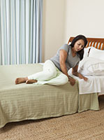 Woman on side in bed, preparing to stand up.