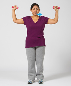 Woman breathing out while doing shoulder press exercise with hand weights.