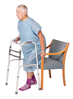 Image of woman with a walker backing up into chair - one hand on walker and one on the arm of the chair - the chair is touching the back of her legs.