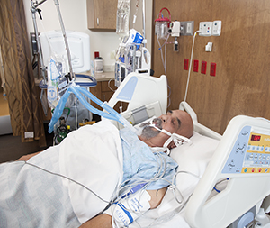 Intubated man in intensive care unit bed.