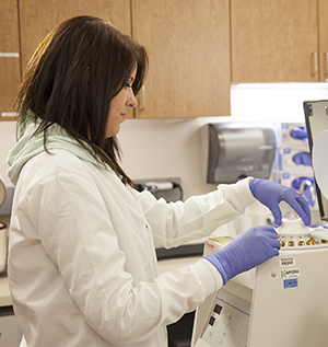 Lab tech with lab equipment and blood samples.