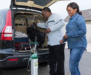 Man and woman loading oxygen tank into back of car.
