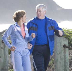 Man and woman outdoors walking in comfortable clothes.