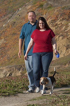 Man and woman outside, walking dog.