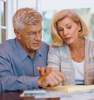 Man and woman sitting at table looking at paperwork.