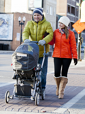 Man and woman walking baby in stroller.