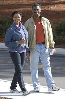 Man and woman walking on sidewalk.