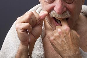 Man flossing teeth.