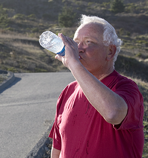 Man drinking water outdoors.