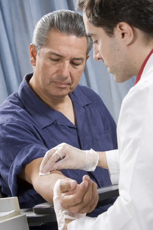 Man having his blood drawn by healthcare provider.