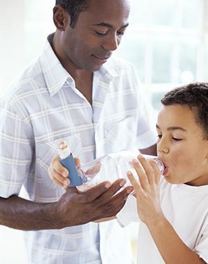 Man helping boy use metered-dose inhaler with spacer.