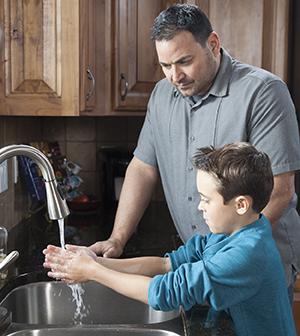 Man helping boy wash hands in kitchen sink.