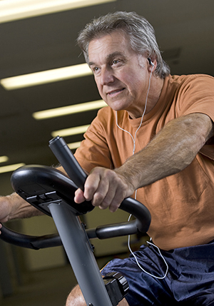 Man holding handles of fitness machine and smiling as he works out.
