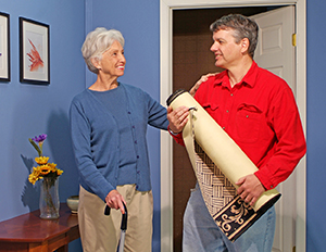 Man holding rolled-up area rug, talking to woman with cane.