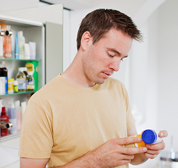 Man looking at pill bottle