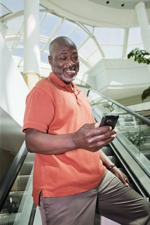 Man on an escalator looking at his phone.