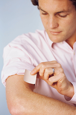 Man placing nicotine patch on arm.