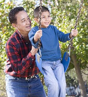 Man pushing boy on swing.