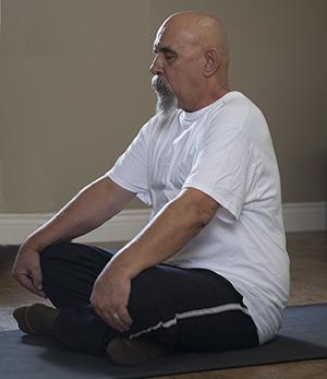 Man sitting in yoga position.