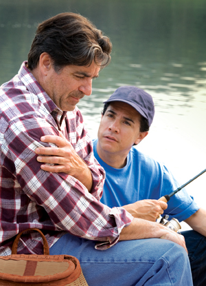 Man sitting next to lake with fishing rod, holding arm and looking distressed. Younger man sitting next to him, looking concerned.
