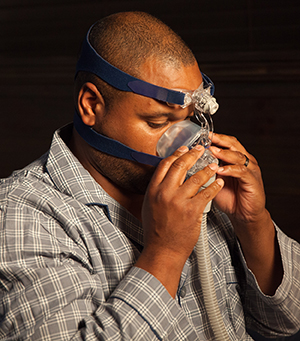 Man sitting on bed, preparing to use CPAP mask and machine.