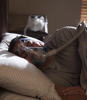 Man sleeping in bed wearing BiPAP mask.