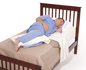 Man sleeping in bed with pillow between his legs.