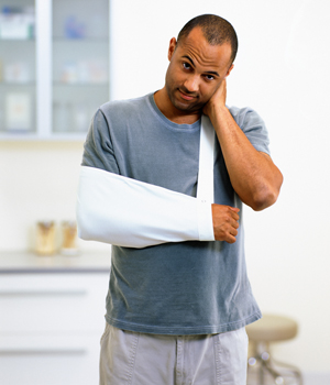 Man standing with his elbow elevated in a sling.