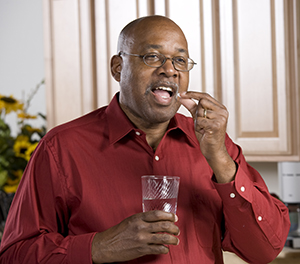 Man taking a pill with a glass of water