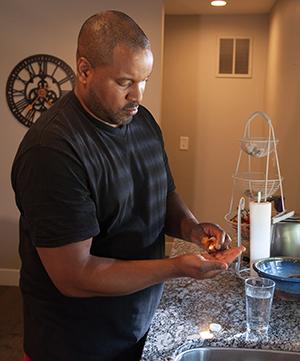 Man taking pill in kitchen.