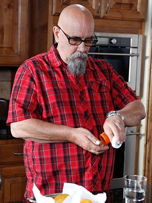 Man taking pills in kitchen.