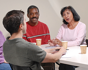 Man talking with counselor and support group.