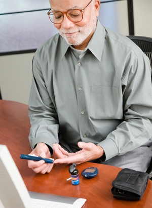 Man using lancet on finger. Glucometer and test strips are on table.