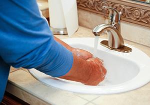 Man washing hands in sink.