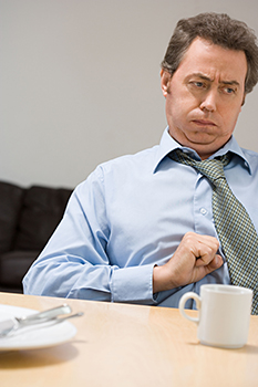 MAn with stomach upset holding his hand to his belly