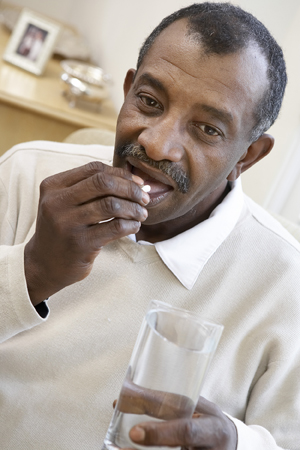 Mature male taking a pill with a glass of water.