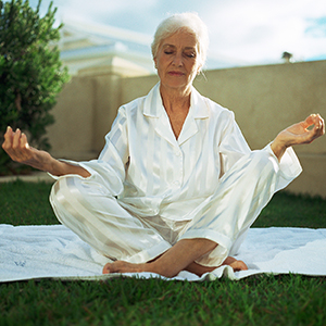 Mature woman outside sitting cross-legged with eyes closed,meditating.