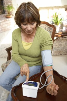 Middle aged woman taking her blood pressure with a home monitor