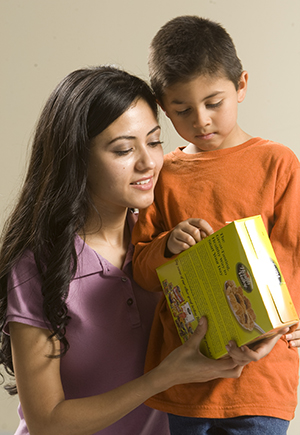 Mom and male child looking at cereal box ingredient information.