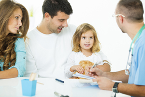 Mother, father, and girl talking to a male healthcare provider.