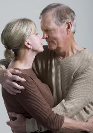 Older man and older woman hugging.