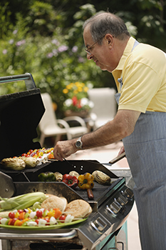 Older man cooking on a grill outdoors