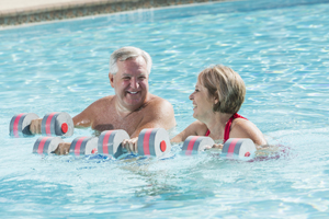 One woman and one man doing water aerobics with weights in pool.