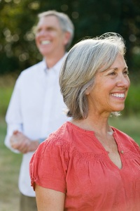 Photo of a smiling middle-aged woman with man in background