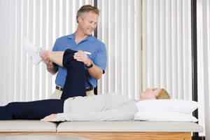 Physical therapist helping patient do knee exercises.